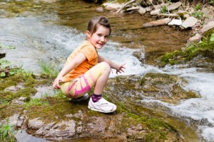 Little girl playing by a forest stream